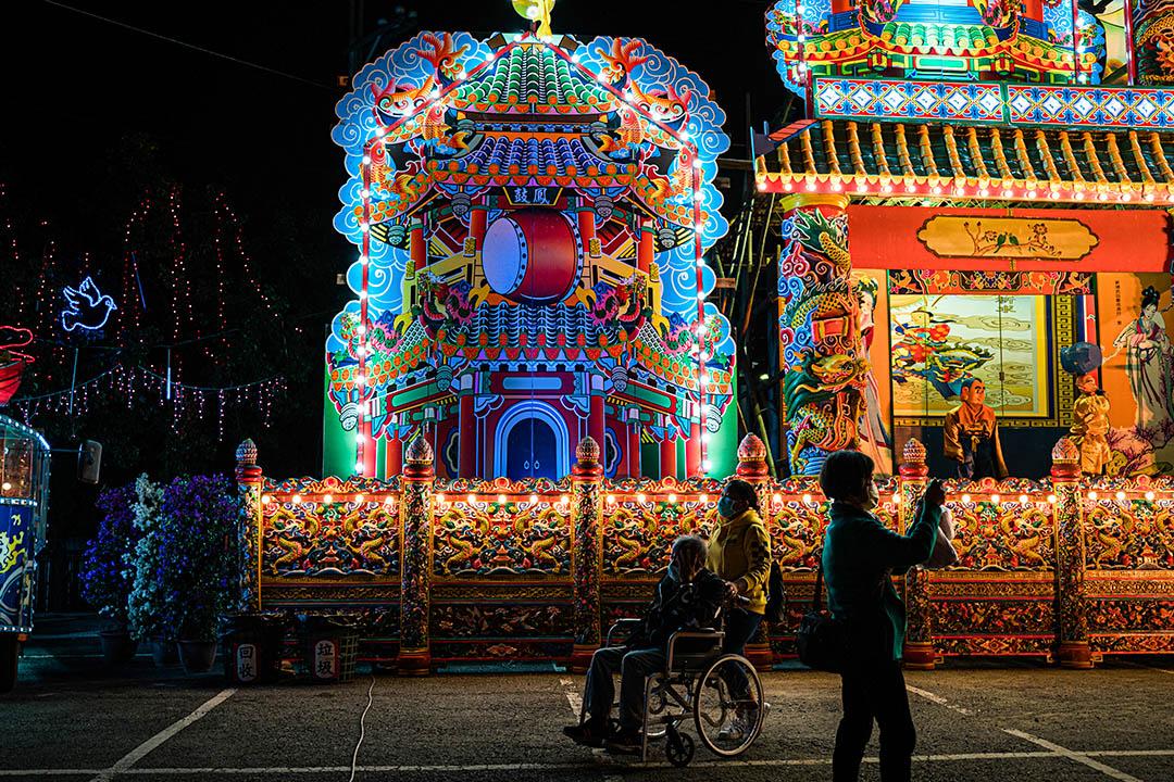 一位鎮上的長者由家人推著輪椅,前往祭典現場。