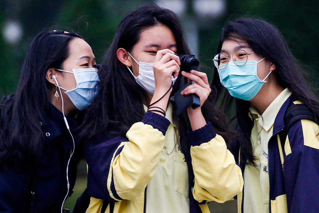 2020年3月11日台北,高中生戴著口罩在中正紀念堂舉行升旗儀式照相。 攝:Ann Wang/Reuters/達志影像