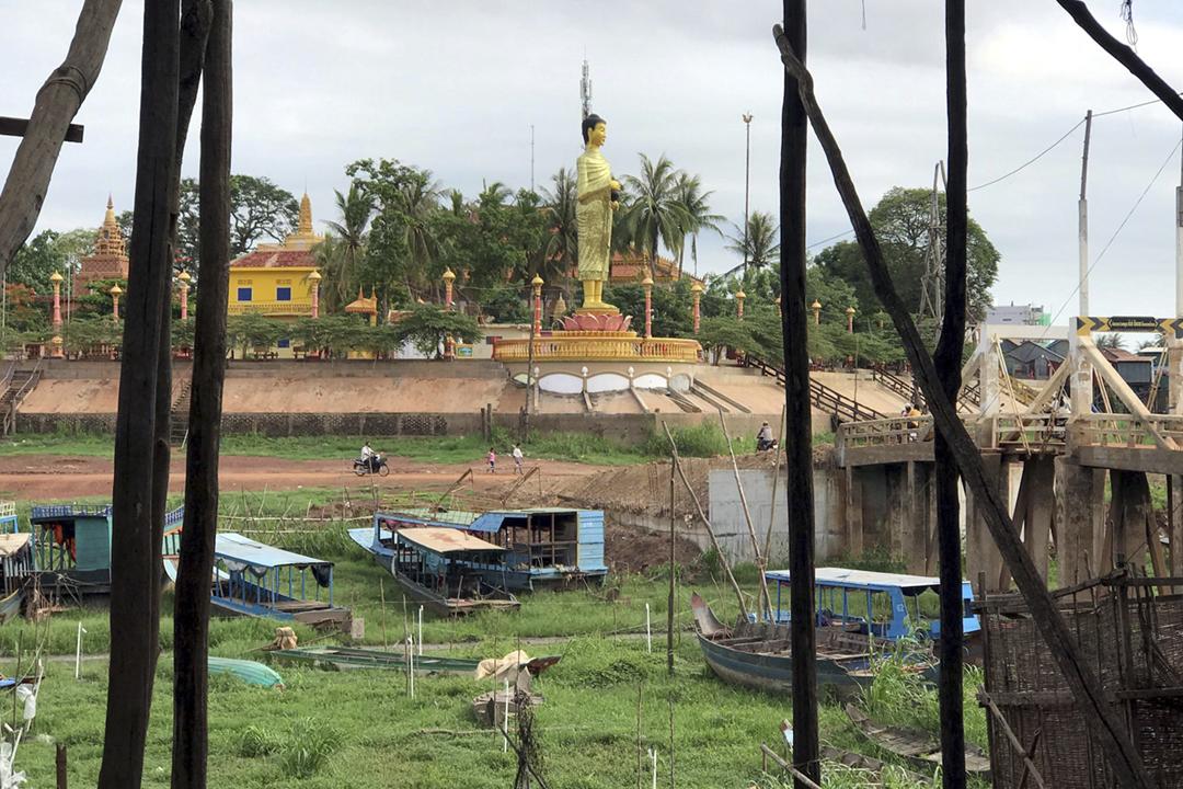 2020年7月6日在柬埔寨,一尊佛像俯視乾涸的洞里薩湖,船隻擱淺於河床。過往在雨季,洞里薩湖因湄公河水回流,面積可擴展至16000平方公里、水深可達九米。 攝:Prak Chan Thul / Reuters