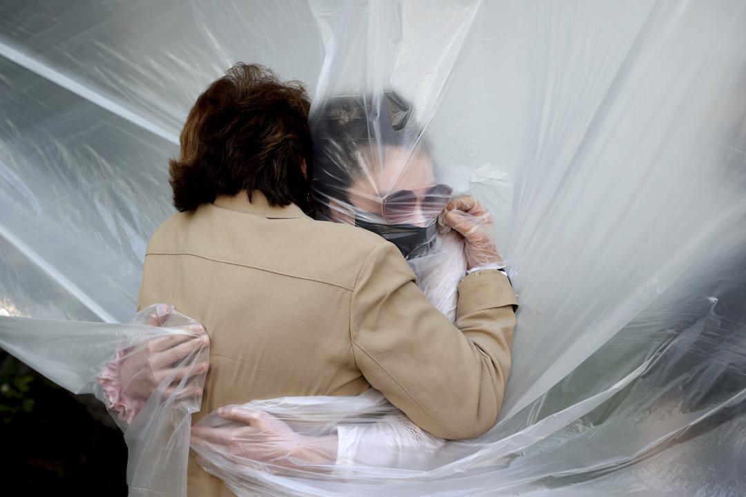 2020年5月24日,美國陣亡將士紀念日,居住在紐約的米歇爾·格蘭特通過塑料布擁抱她的母親瑪麗·格蕾絲·西利奧,自從2月新冠病毒爆發後,這是她們第一次進行的身體接觸。 攝: Al Bello/Getty Images