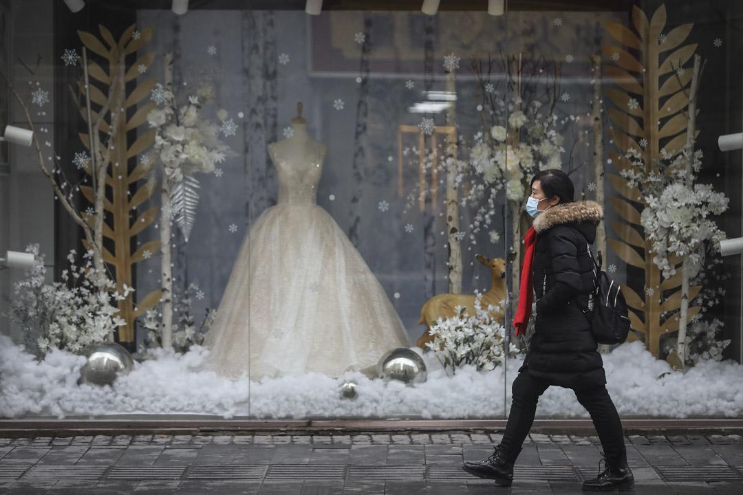 2020年1月22日,武漢一名女士在婚紗店前經過。