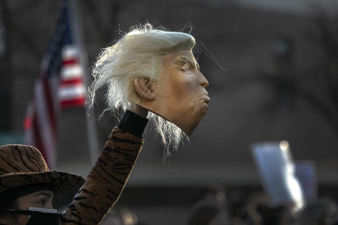 2020年11月7日,美國密歇根州底特律市,有遊行要求美國總統特朗普承認大選落敗,一名參加者舉起一個特朗普造型面具。