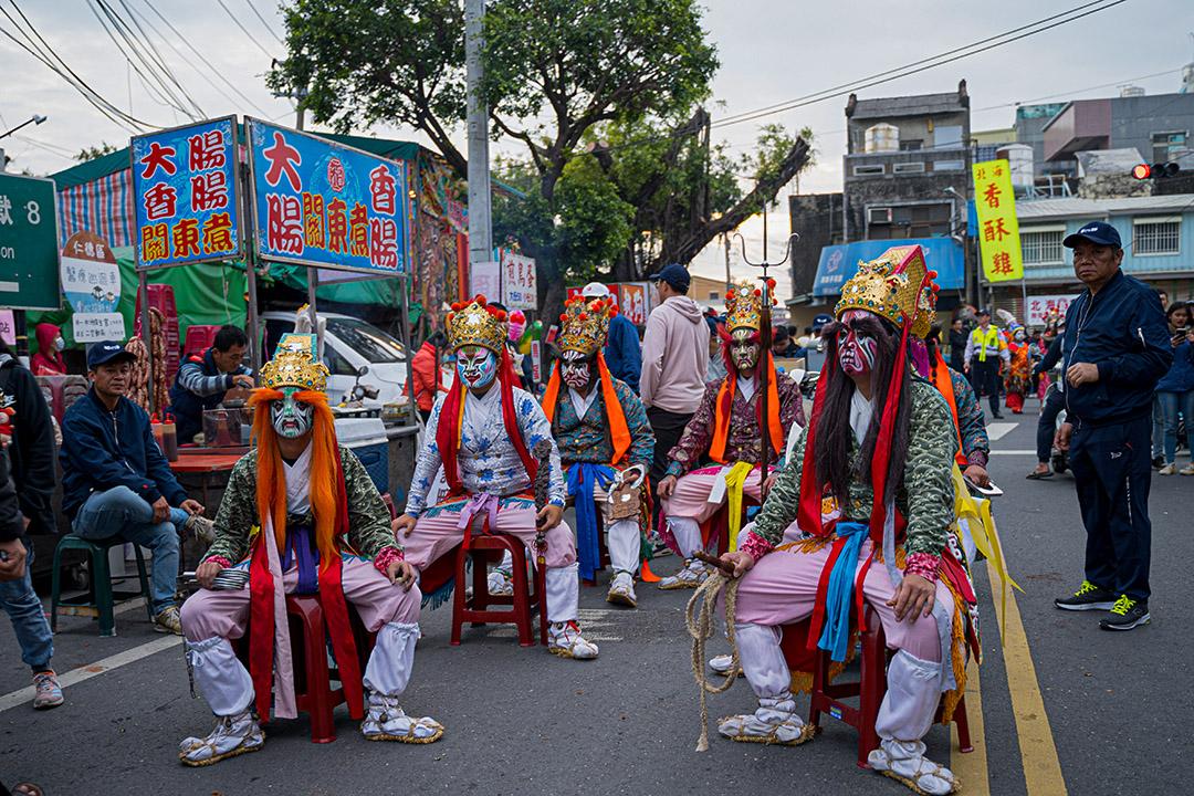 一群官將首在途中稍事休息。祭典所及之處,都會吸引攤販聚集,形成流動的小型夜市。
