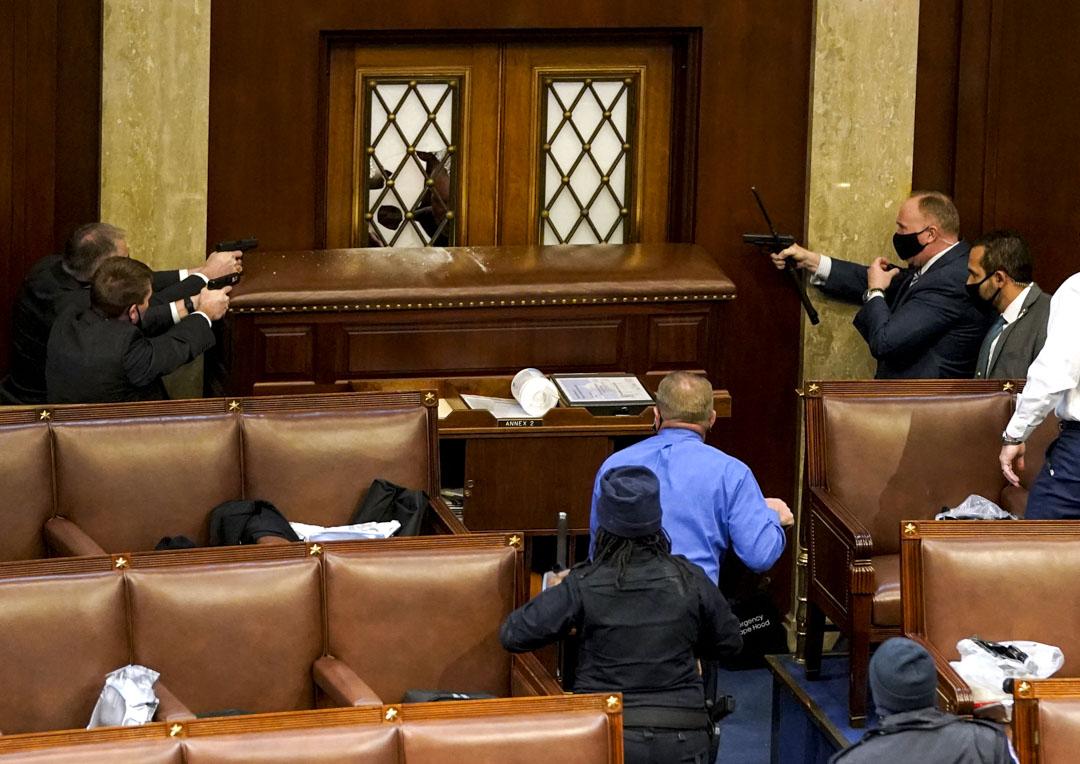 2021年1月6日,美國國會,參眾兩院會議進行期間,示威者闖進國會大樓,破壞參議院大門,國會警察持槍戒備。