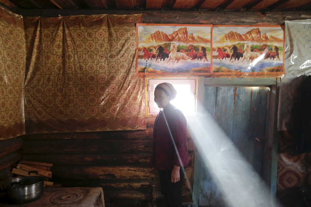 2018年1月27日在新疆,一位村民站在家中窗前。 攝:Jason Lee / Reuters