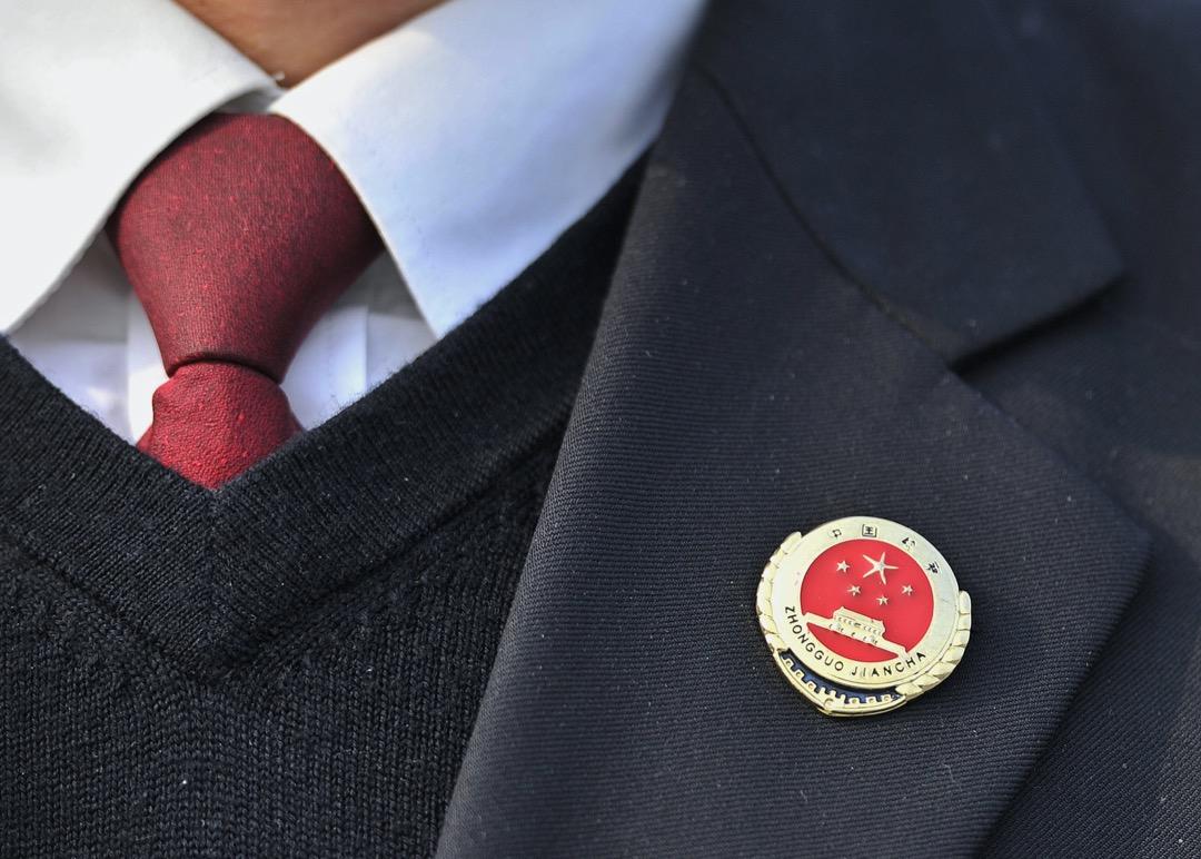 2014年3月,第十二屆全國人民代表大會第二次會議,一名與會者扣上一個國徽襟章。