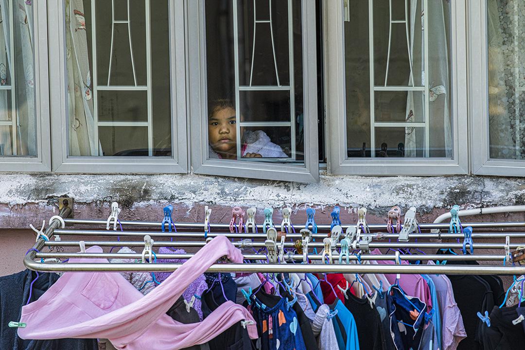 2021年1月25日油麻地,封鎖區內一名兒童在家窗邊望向街外。 攝:陳焯煇/端傳媒