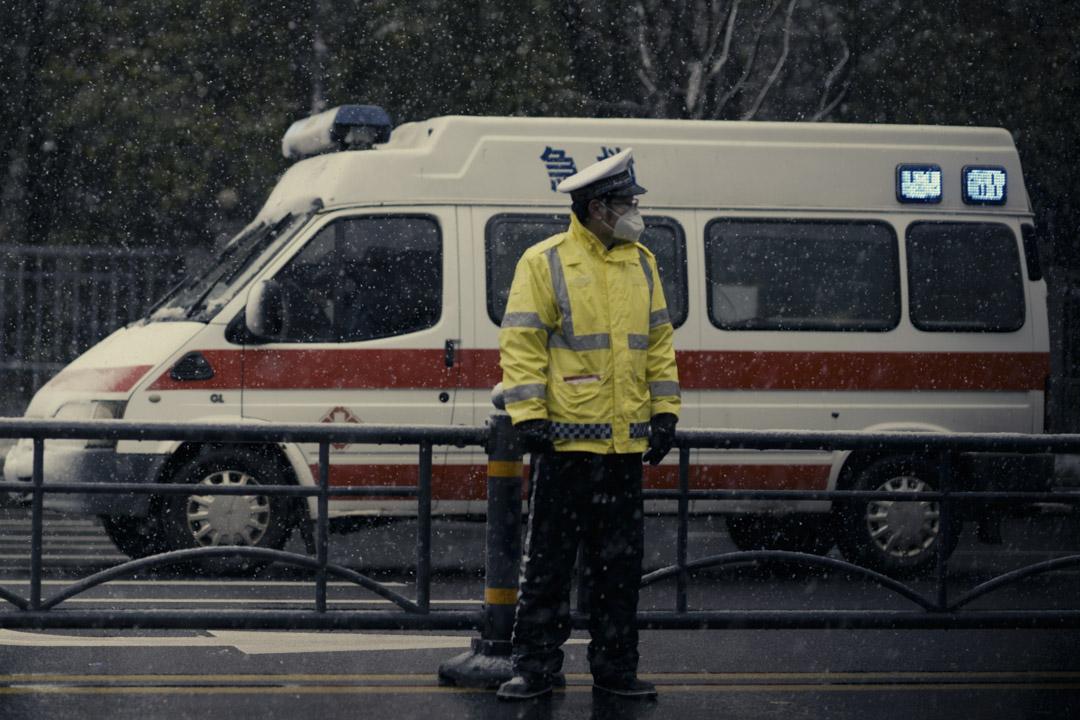 救護車前的一位戴上口罩的交通警察。