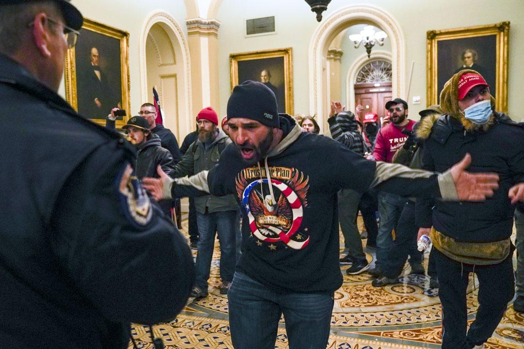 2021年1月6日,美國國會,一名特朗普支持者在參議院會議廳外向一名國會警察示意。
