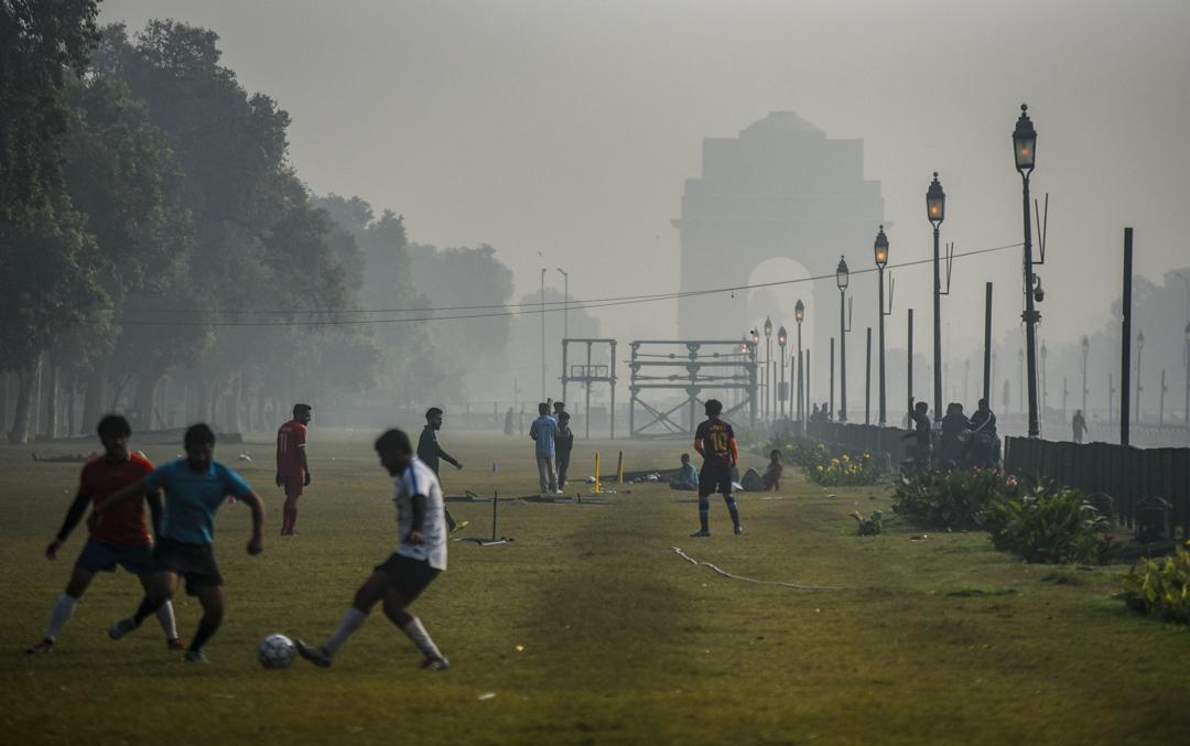 2020年12月6日,印度新德里被霧霾籠罩,人們繼續在草坪上踢足球。