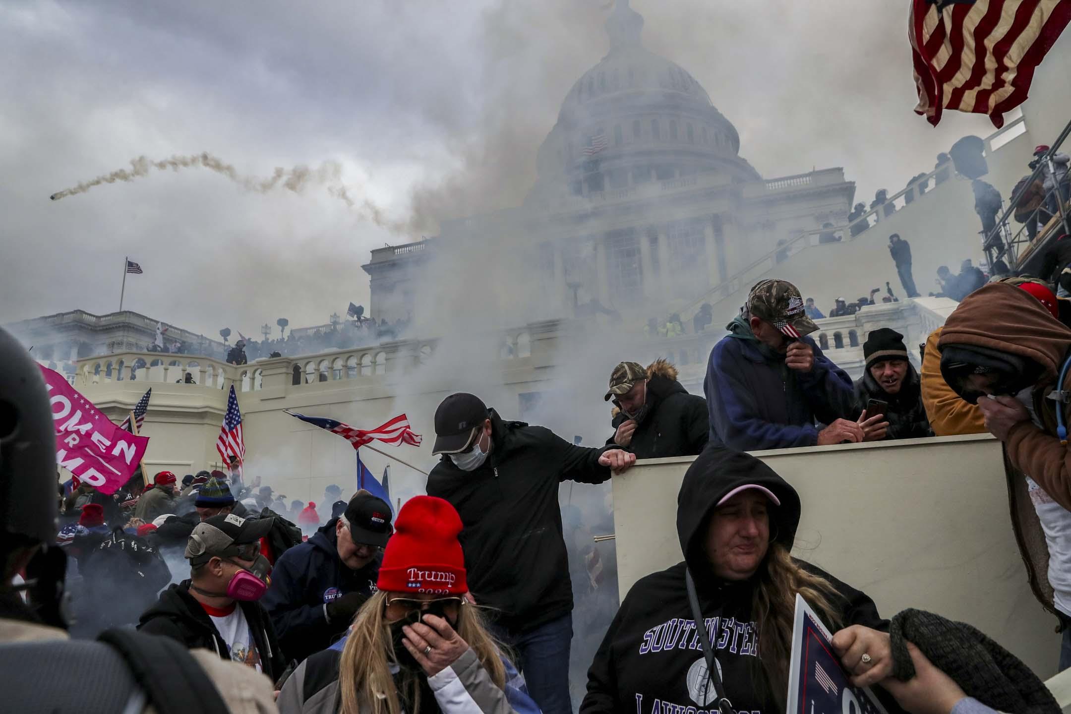 2021年1月6日,華盛頓美國國會大樓前,特朗普支持者與警察發生衝突,後方警方發射催淚彈驅散。 攝:Leah Millis /Reuters/達志影像