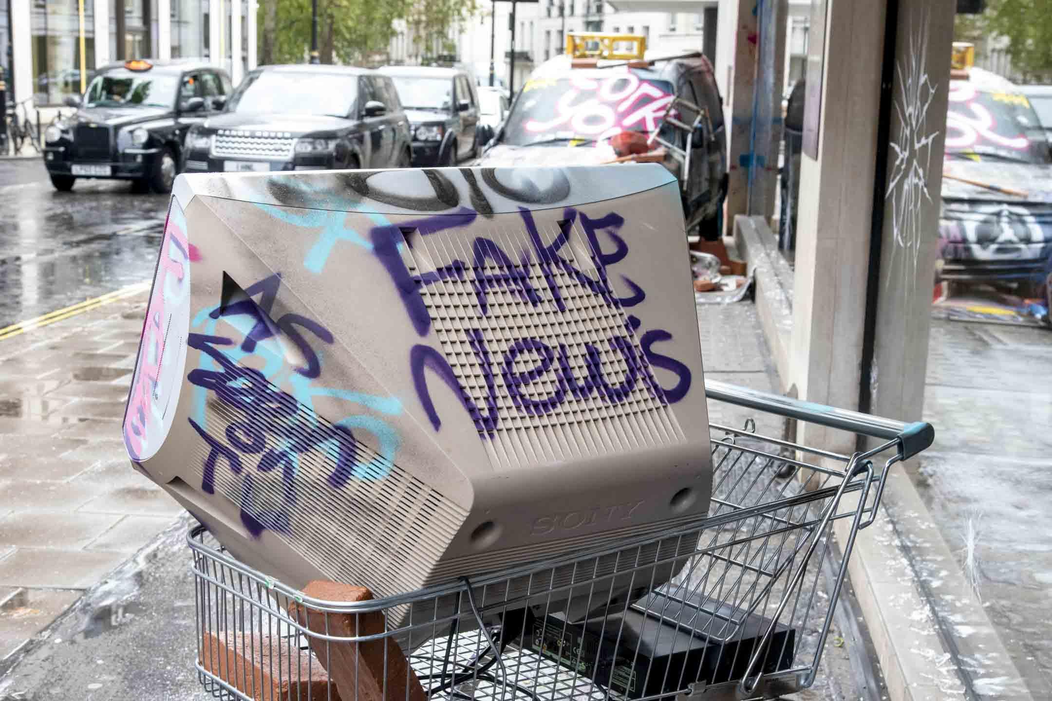 2020年10月8日,倫敦街上有架購物手推車上有一台電視,上面印有「假新聞」字樣。