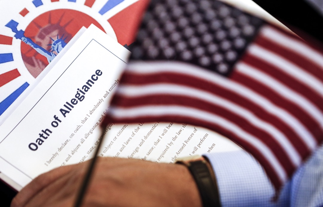 美國首都華盛頓特區,一場入籍美國的歸化儀式上,一名參與者手持一份《效忠誓詞》及一支美國國旗。