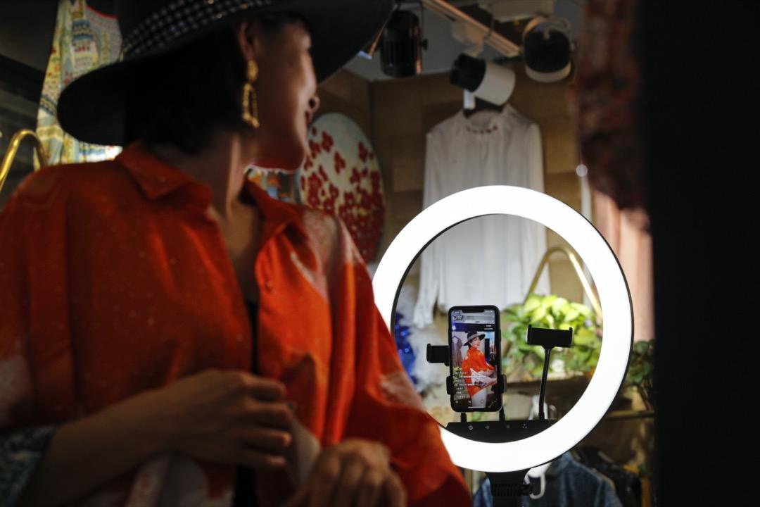 2020年4月27日,北京一家時裝店的店主透過直播軟件在店內為她的顧客展示新款時裝。