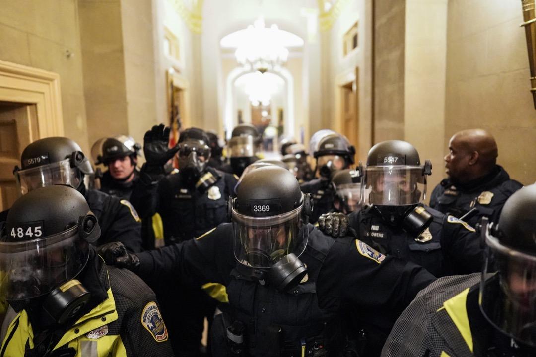 2021年1月6日,特朗普支持者不滿總統選舉結果,闖進國會大廈抗議,國會警察在大樓走廊間築起防線。