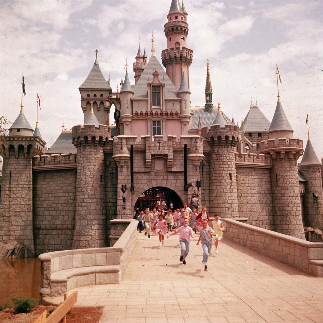 1955年,兒童在迪士尼主題公園的睡美人城堡大門前奔跑。