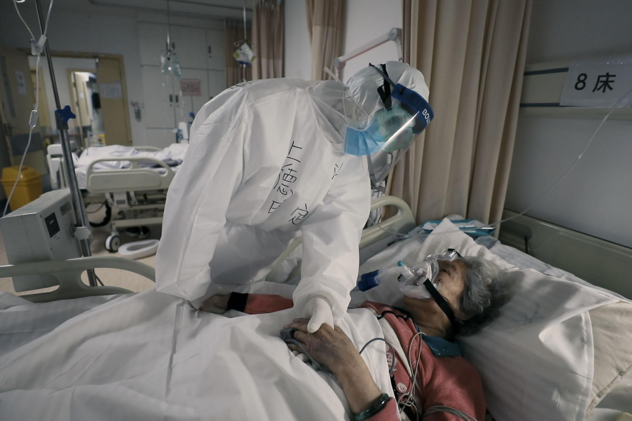 一名護士照顧患有新冠病毒的老太太。
