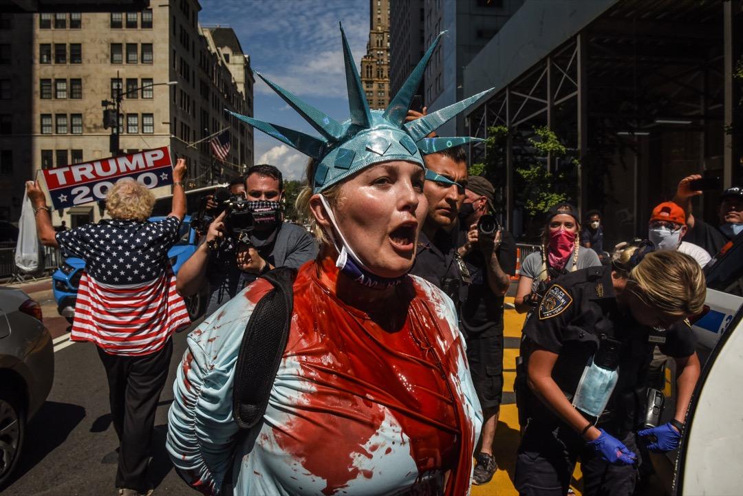 2020年8月23日,美國紐約市,一名裝扮成自由神像的女子,到曼哈頓第五大道特朗普大樓外,向地上的「Black Lives Matter」標語潑紅色油漆後被警方帶走。 攝:Stephanie Keith/Getty Images