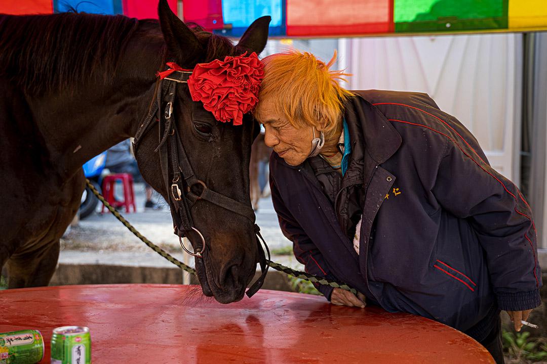 一名信眾與他當日負責照顧的馬匹相互依偎。