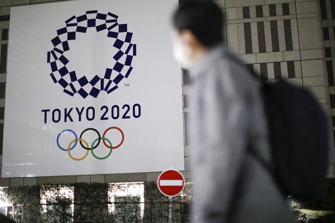 2021年1月22日在日本東京,一名配帶口罩的男子經過東京奧運的大型宣傳海報。 攝:Issei Kato / Reuters