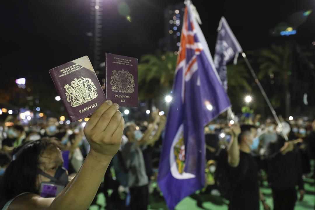 2020年6月4日在香港,一名出席「六四事件燭光悼念晚會」的港人舉起「英國國民(海外)護照」,身邊則有人舉起港英殖民時期的「香港旗」。 攝:Tyrone Siu / Reuters