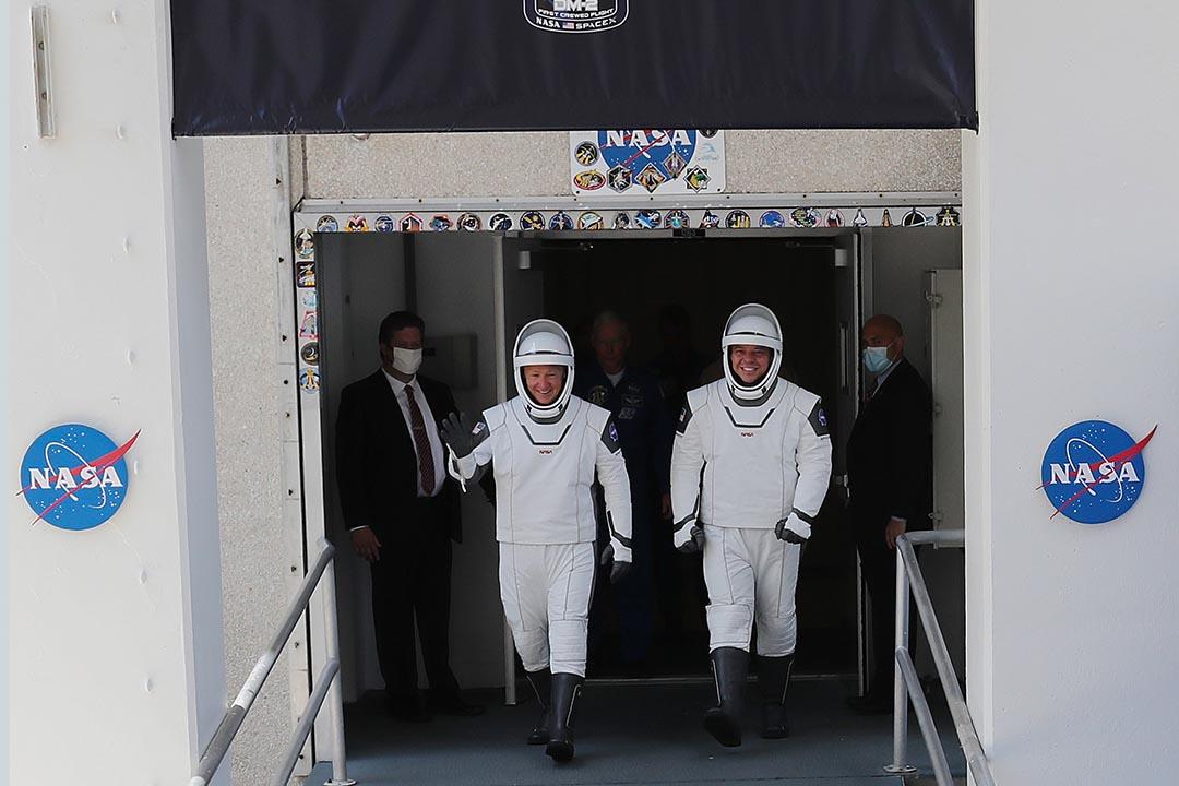 2020年5月30日美國開普敦,宇航員鮑勃·貝肯(右)和道格·赫利(左)走出大樓,前往獵鷹9號運載火箭。