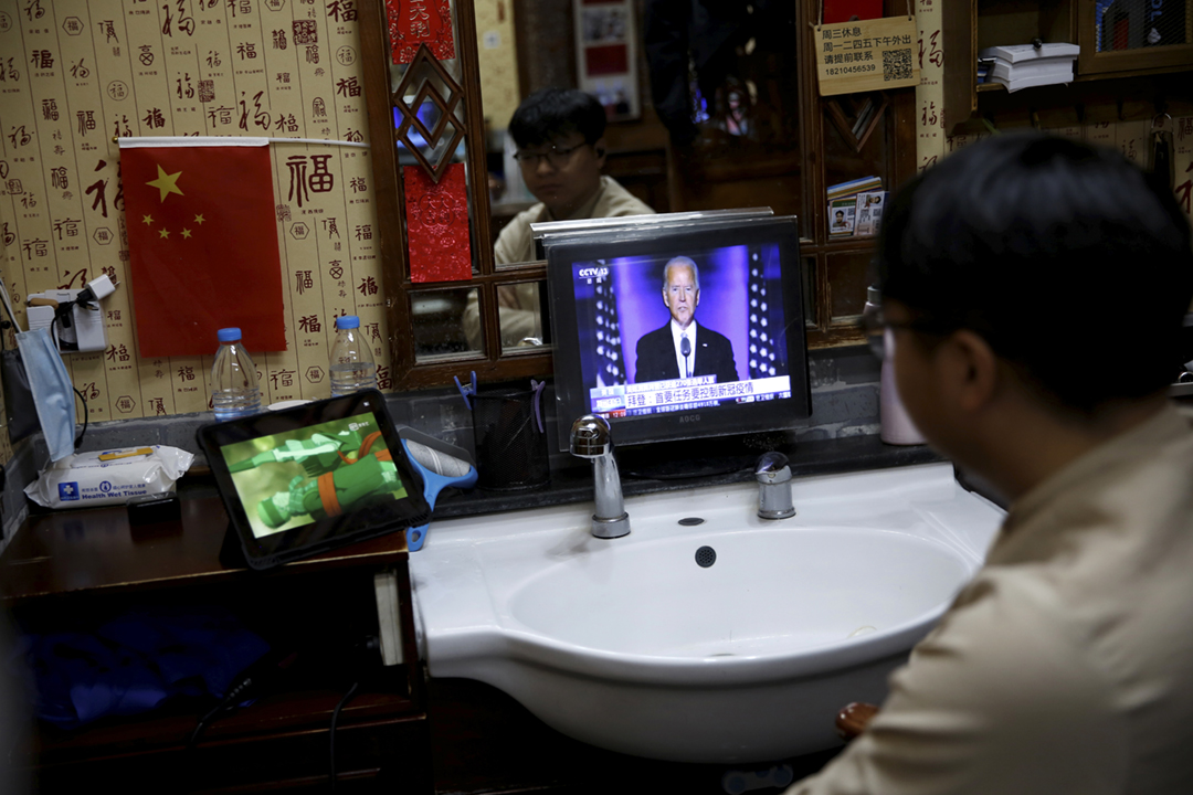 2020年11月8日在中國北京的一家理髪店內,一名店員正以平板電腦收看拜登發表講話,當時拜登尚未正式確認當選美國總統。 攝:Tingshu Wang / Reuters
