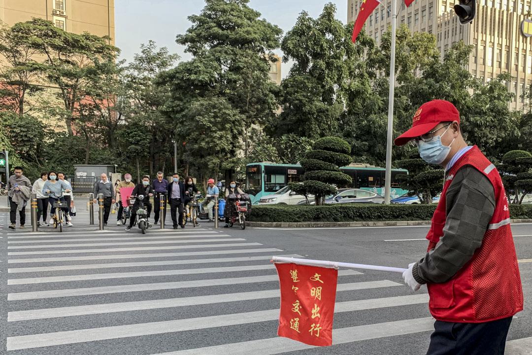 街道辦的指揮交通志願者。