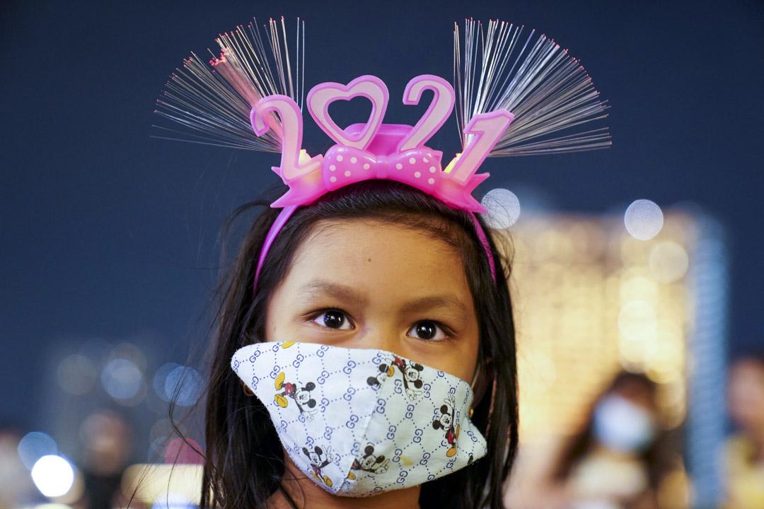 2020年12月31日,泰國曼谷一位戴著口罩和「 2021」頭飾的女孩。 攝:Athit Perawongmetha/Reuters/達志影像