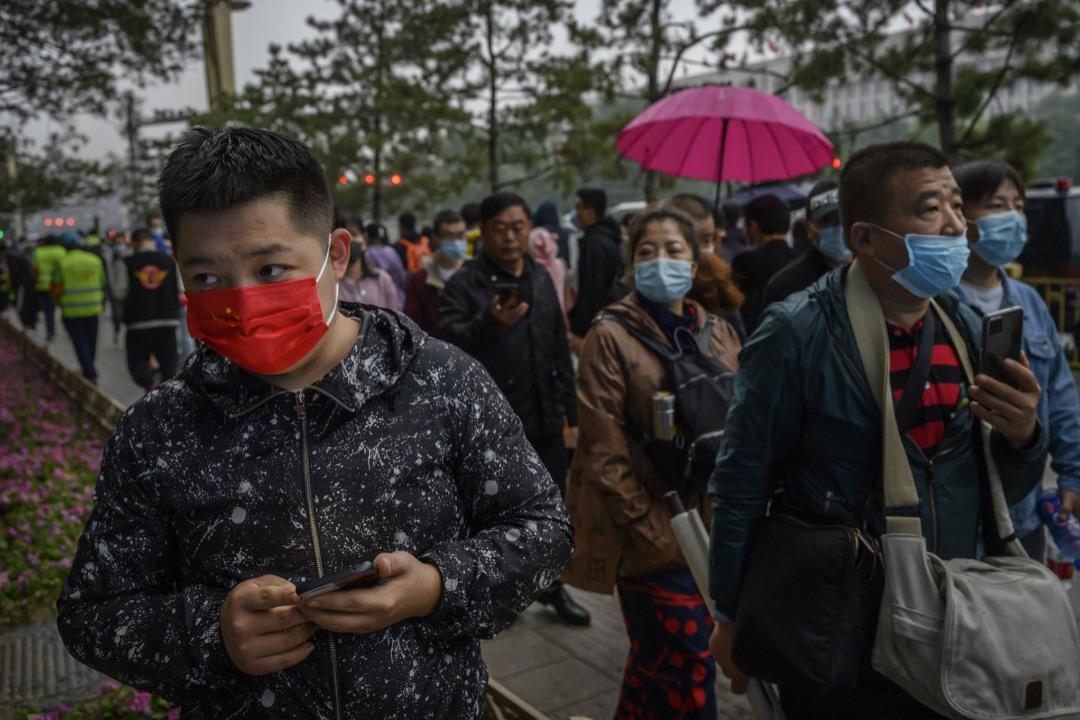 2020年10月,北京,一名戴上紅色口罩的男子在街道上走過。