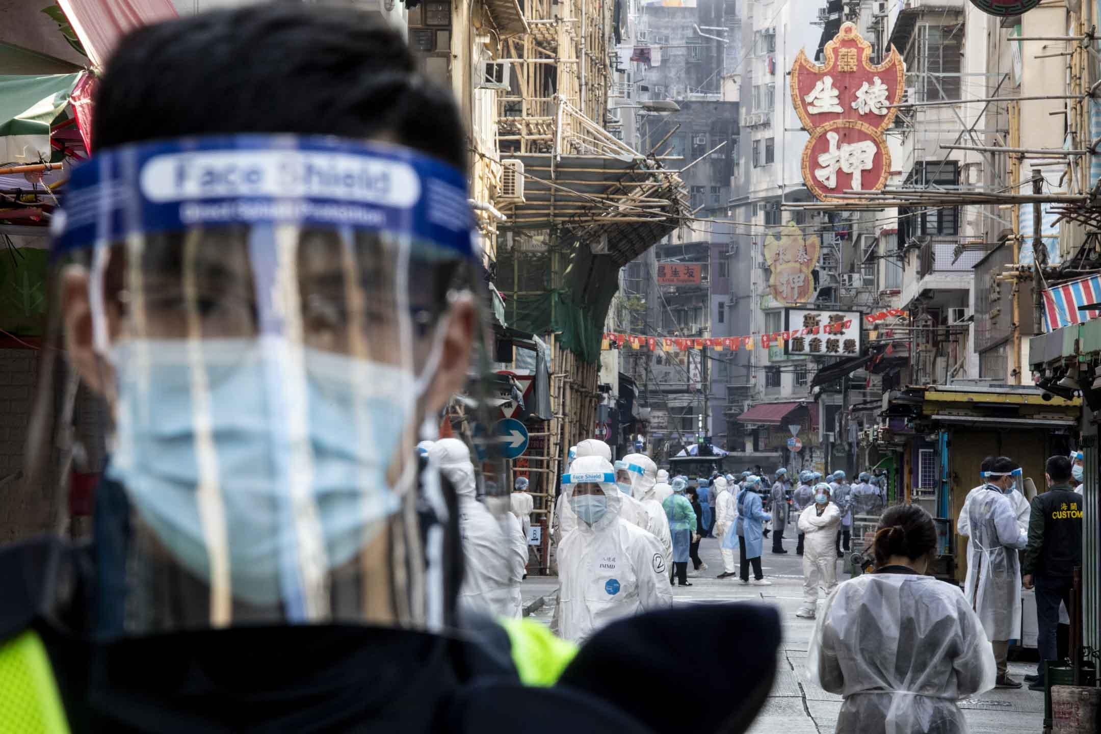 2021年1月23日,佐敦「受限區域」由警員把守出入口,內有大量穿上保護衣的工作人員安排區內人士強制檢測。 攝:林振東/端傳媒