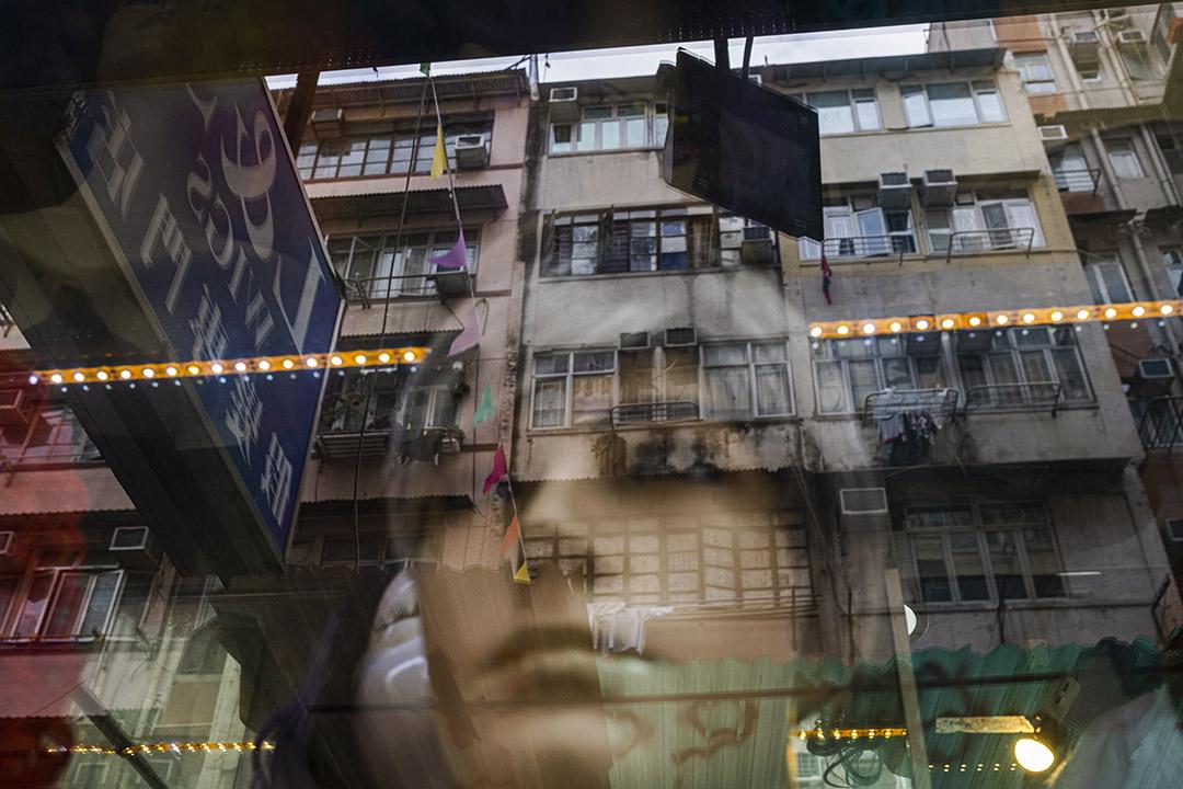 2021年1月19日廟街,一間髮型用品店的玻璃倒影著一幢唐樓。
