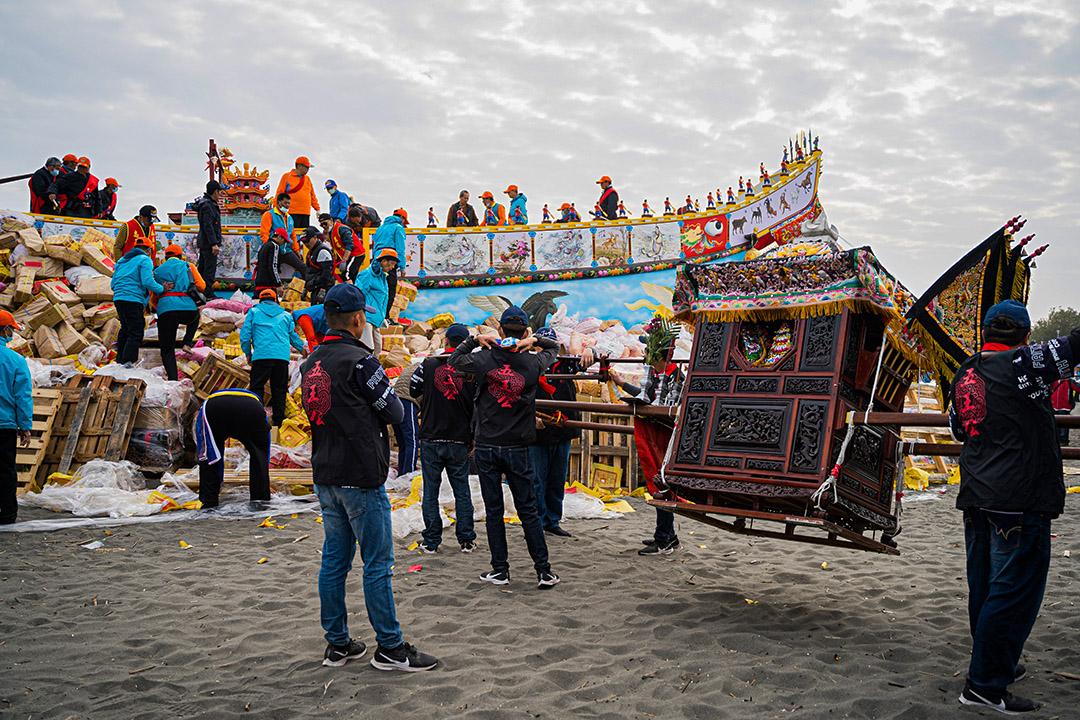 海灘上的王船,由信眾合力放上添儎物資及金紙堆,準備隨王船焚燒昇天,以完成送王儀式。