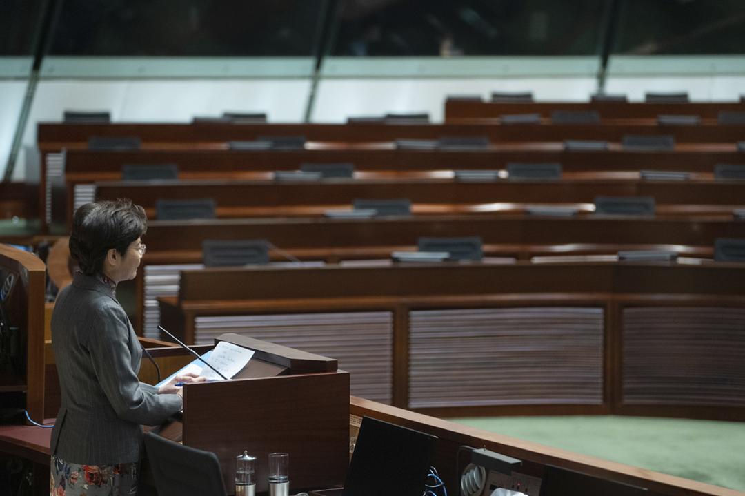 2020年11月26日,香港特首林鄭月娥在立法會出席答問環節,泛民主派當時已因不滿中方 DQ 四名議員而宣佈總辭,會議廳內一片席位空缺。 攝:Roy Liu / Bloomberg via Getty Images