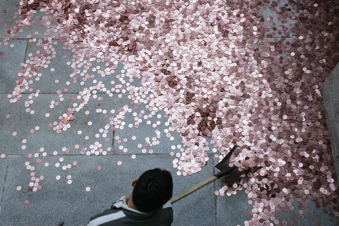 2007年,北京,白雲觀的一位員工在清理市民為祈福拋出的硬幣。