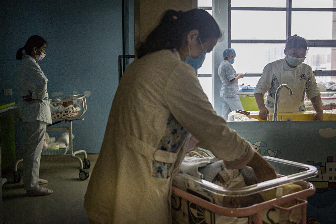 2020年3月12日武漢,一名產婦護士戴著口罩在一家私立醫院產科照顧新生兒。