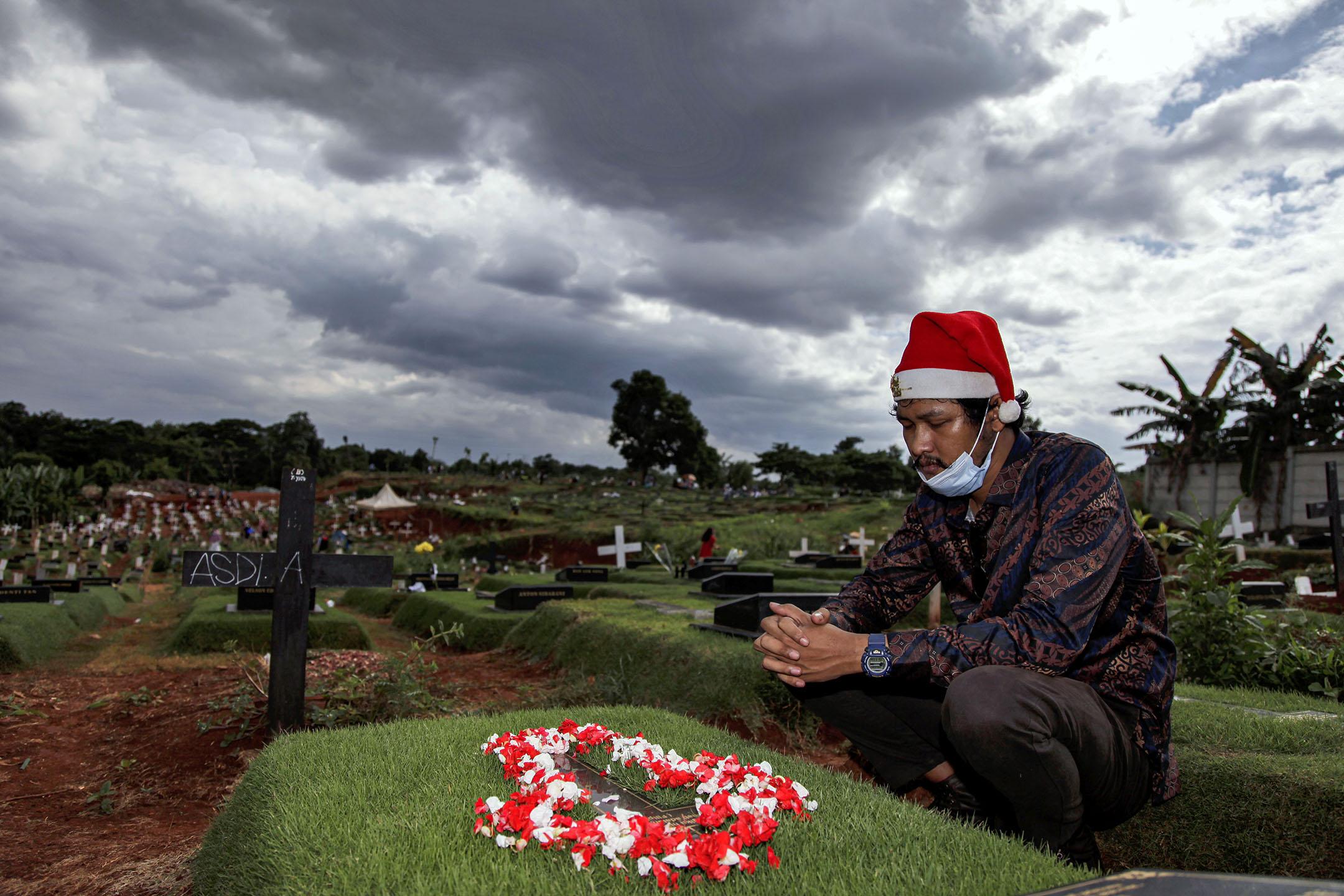 2020年12月25日印尼東雅加達,戴著口罩和聖誕帽的男人向墳墓拜祭,他的家人死於2019冠狀病毒。 攝:Aditya Irawan/NurPhoto via Getty Images
