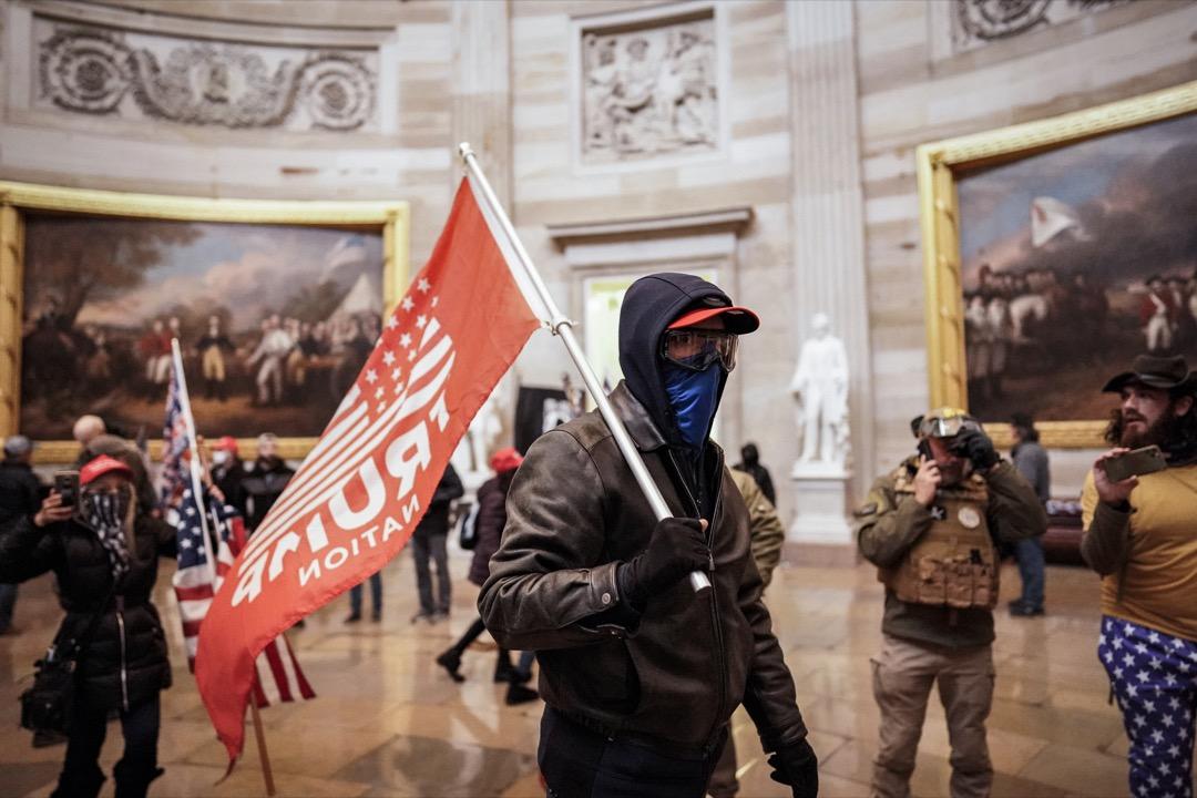 2021年1月6日,一名特朗普支持者闖進國會大廈後,拿著旗幟走過圓形大廳。