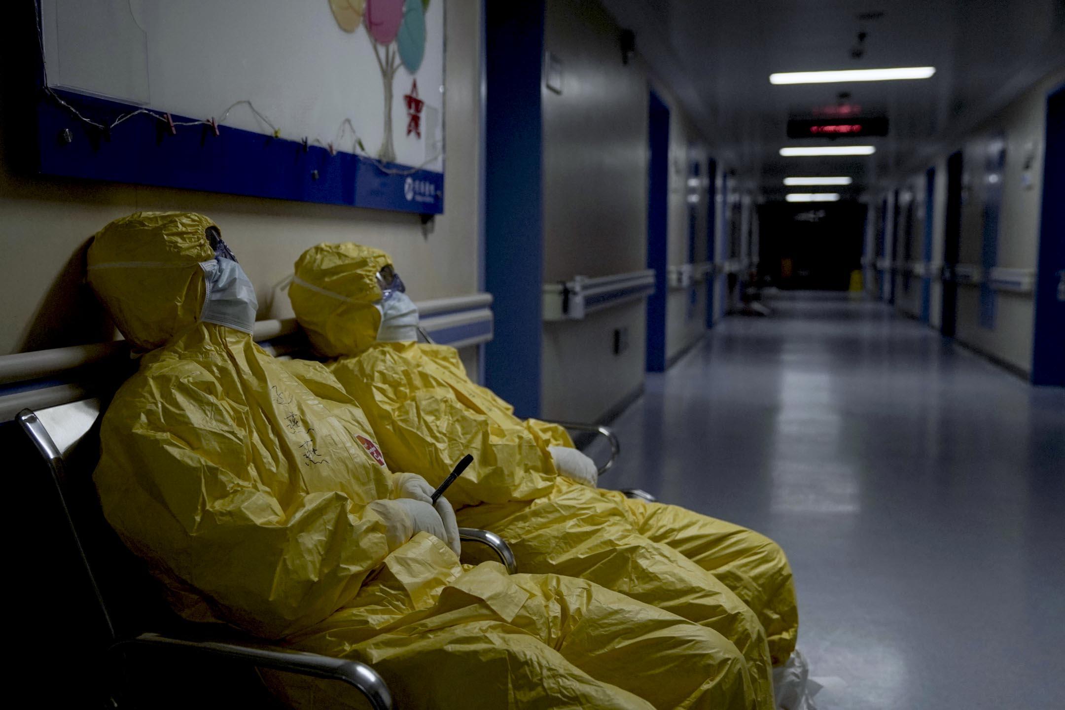兩名筋疲力盡的醫務人員在醫院長凳上休息。