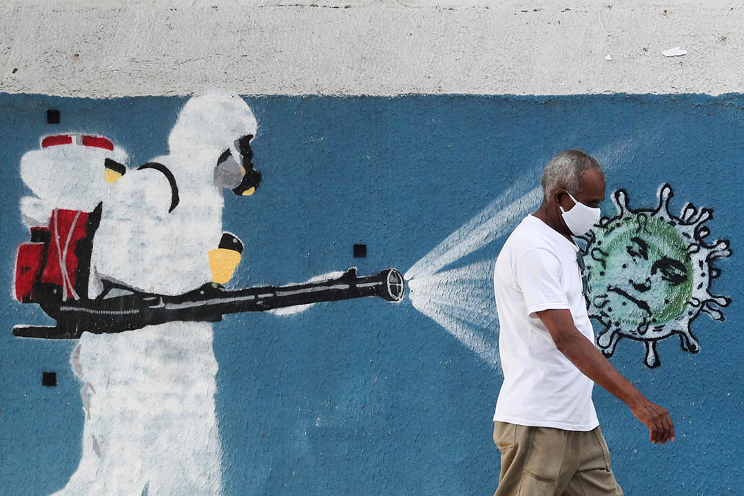 2020年6月12日巴西里約熱內盧,一名男子走在巴西總統博索納羅(Jair Bolsonaro)塗鴉旁。