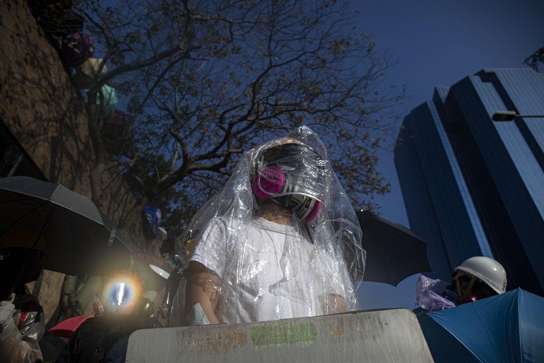 2019年11月17日香港 ,示威者佔領香港理工大學,一名示威者用塑膠覆蓋自己,防止水炮車的藍色染色液體。