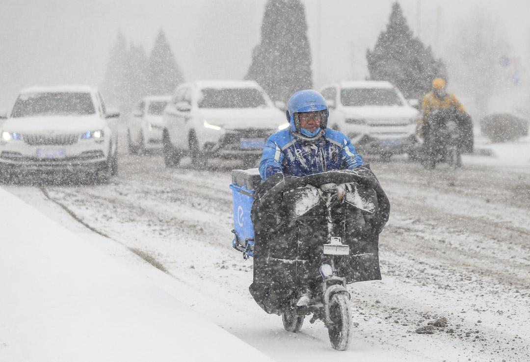 2021年1月6日,遼寧暴風雪期間,餓了麼外賣員在公路駕車送餐。