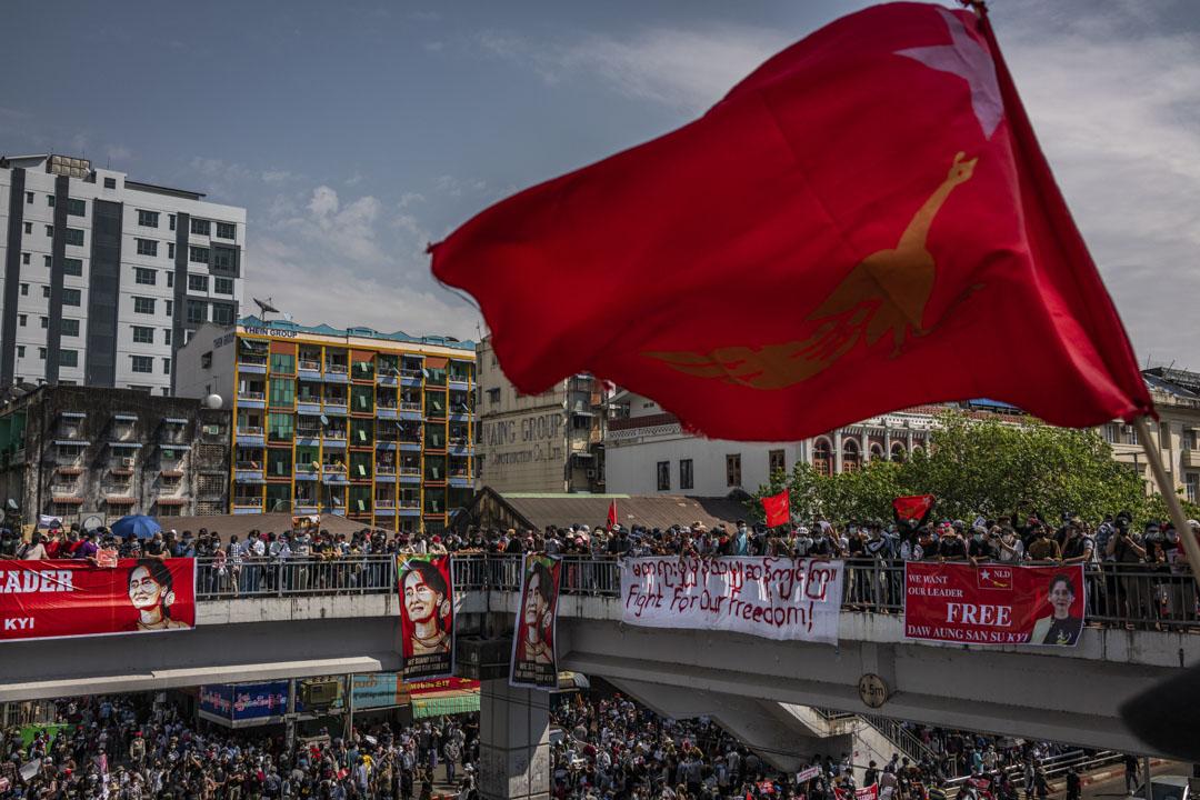 2021年2月08日,示威者在緬甸仰光市中心遊行時以舉起三指致敬,並舉起橫幅和全緬學生會的旗幟。