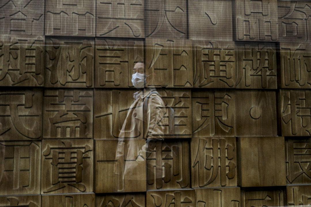 2020年10月14日,一名戴著口罩的女士在北京一家商店前走過。
