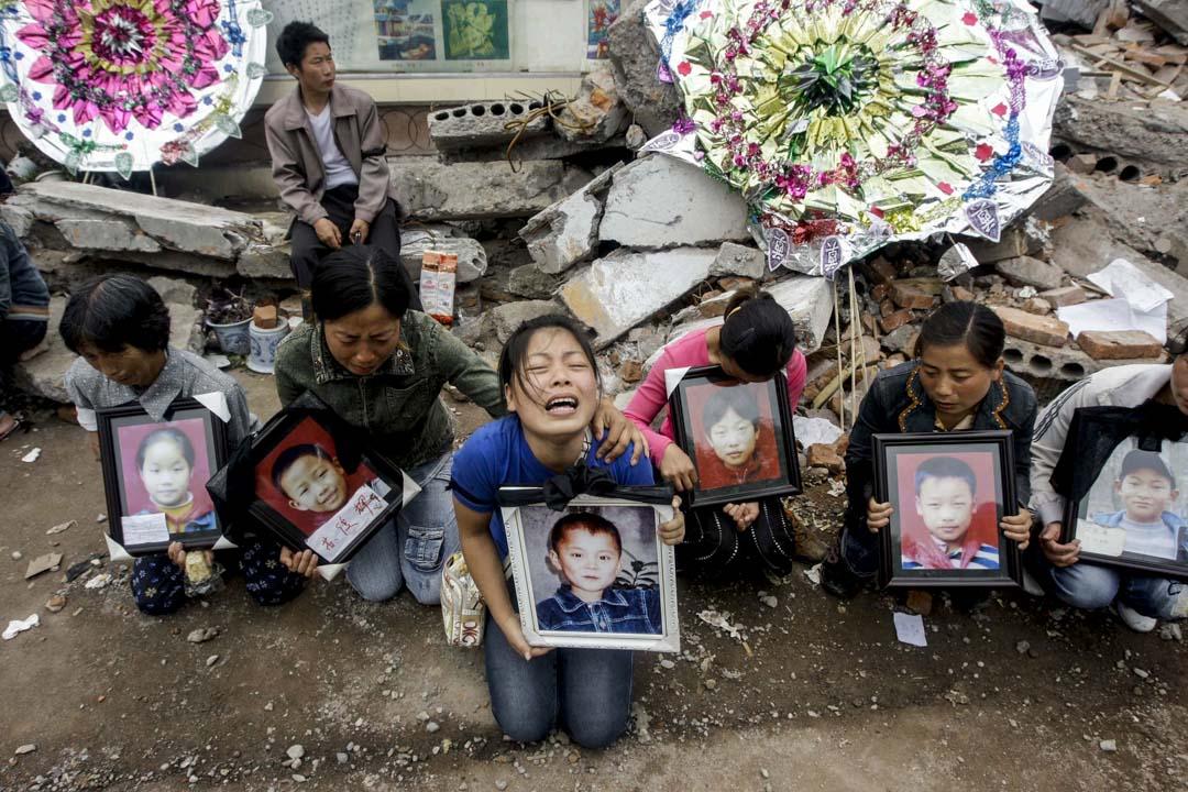 2008年5月21日,四川綿竹一間因地震倒塌的小學遺址上,一名母親手持兒子的肖像哭起來。