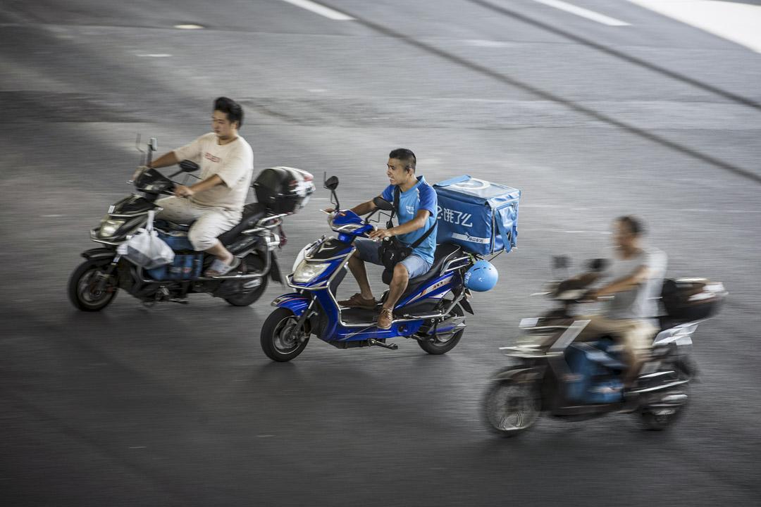 2018年8月20日,餓了麼送貨車手在上海公路上駕著電單車送外賣。 攝:Qilai Shen/Bloomberg via Getty Images