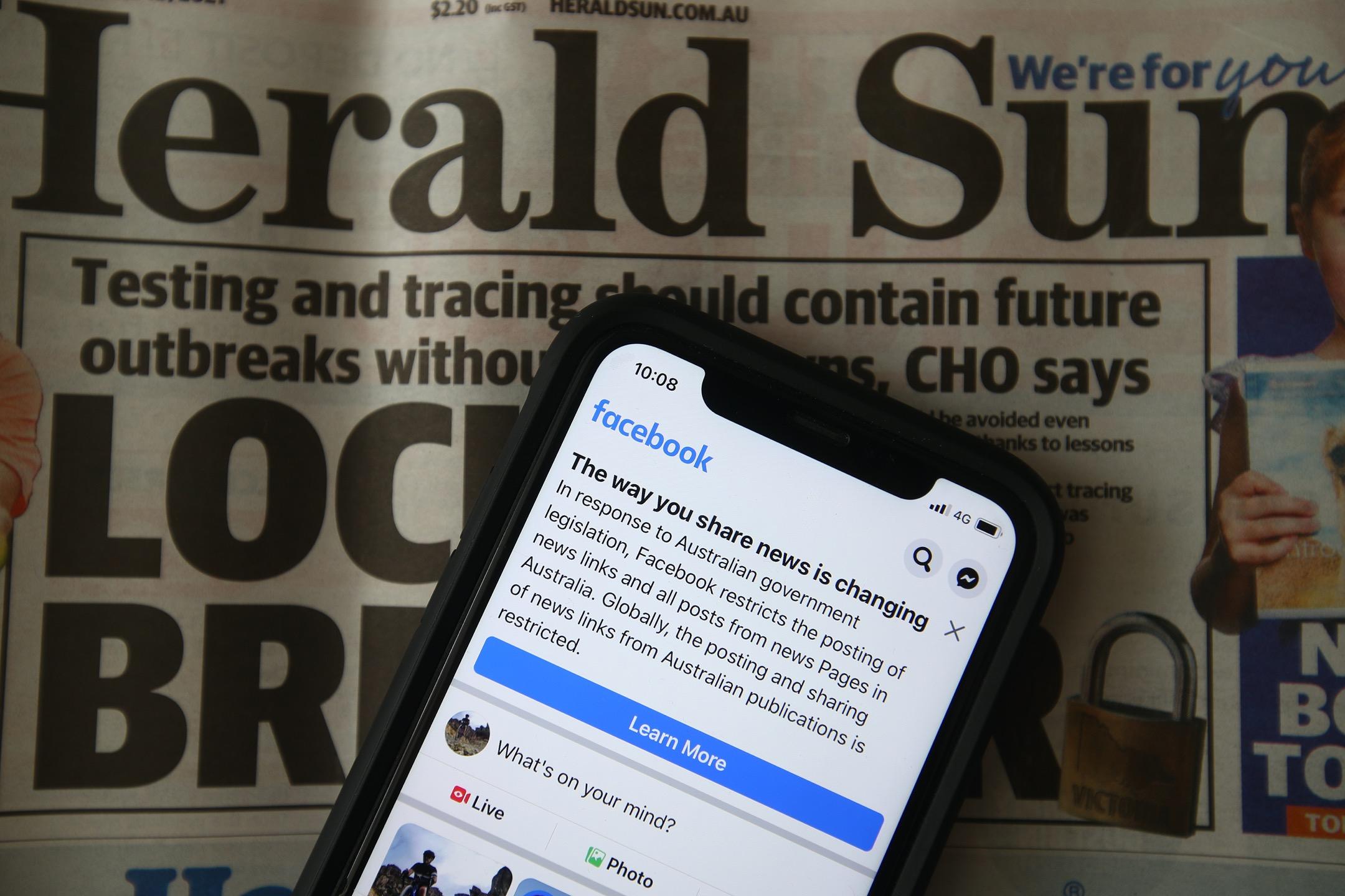2021年2月18日的《先驅太陽報》,上面的智能電話顯示著Facebook禁止澳洲用戶分享新聞內容的通知。 攝:Robert Cianflone/Getty Images