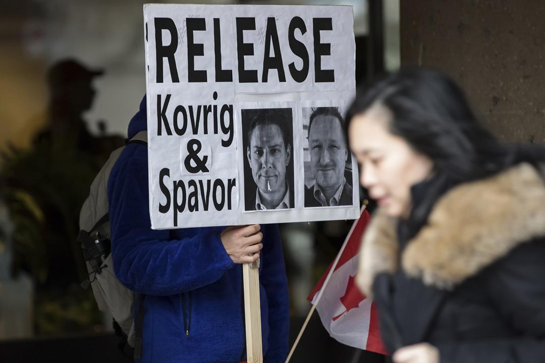 2020年1月21日在加拿大溫哥華卑詩省最高法院外,一名男子舉起標語,要求中方釋放前外交官康明凱(Michael Kovrig)及商人斯帕弗(Michael Spavor)。 攝:Darryl Dyck / The Canadian Press via AP