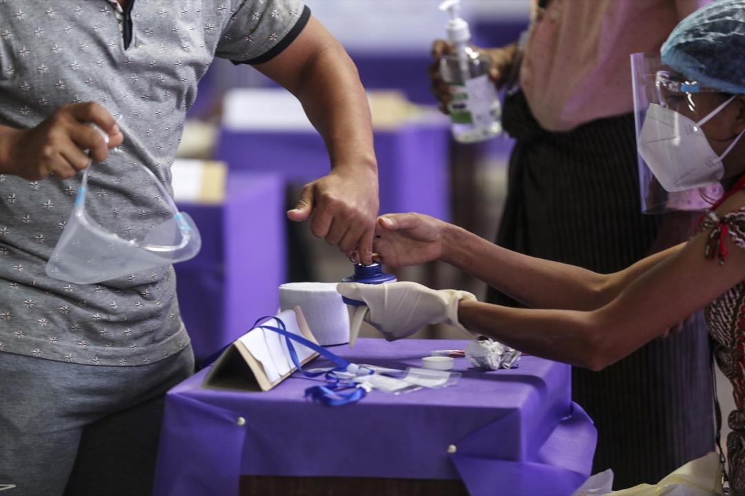 2020年11月8日,緬甸舉行大選,選民在票站職員協助下把手指頭染藍,表示已經完成投票。