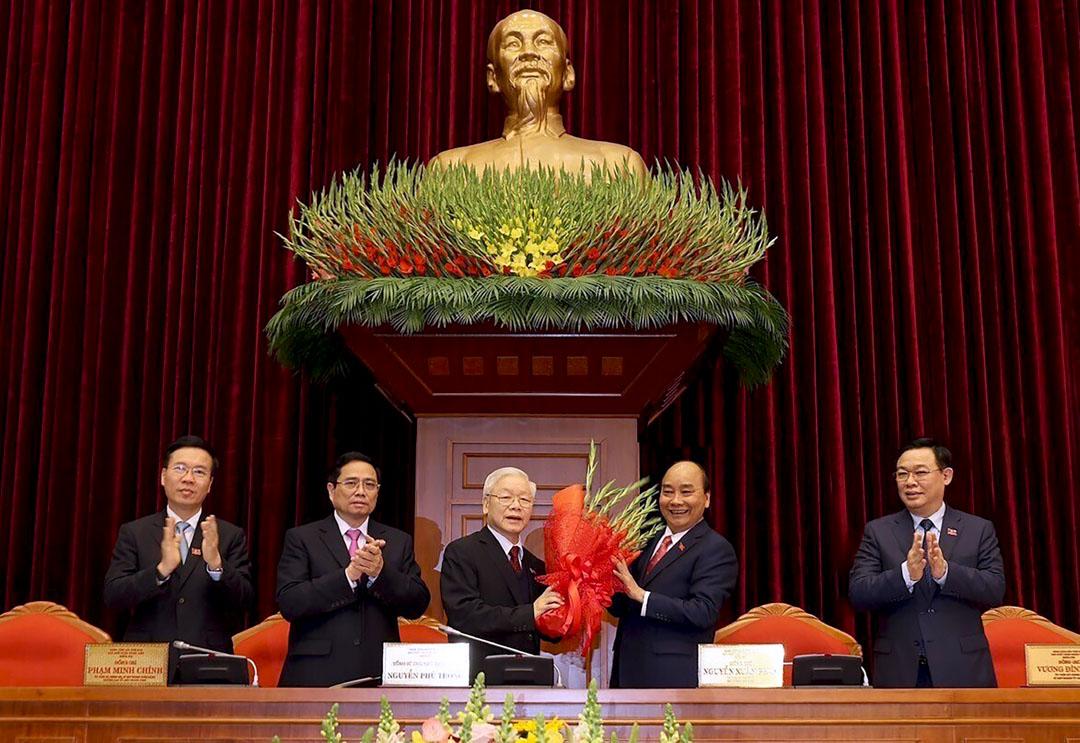 2021年1月31日,現年77歲的阮富仲再度連任越南共產黨總書記一職,總理阮春福向他獻上花束。 攝:Le Tri Dung/VNA via AP/達志影像